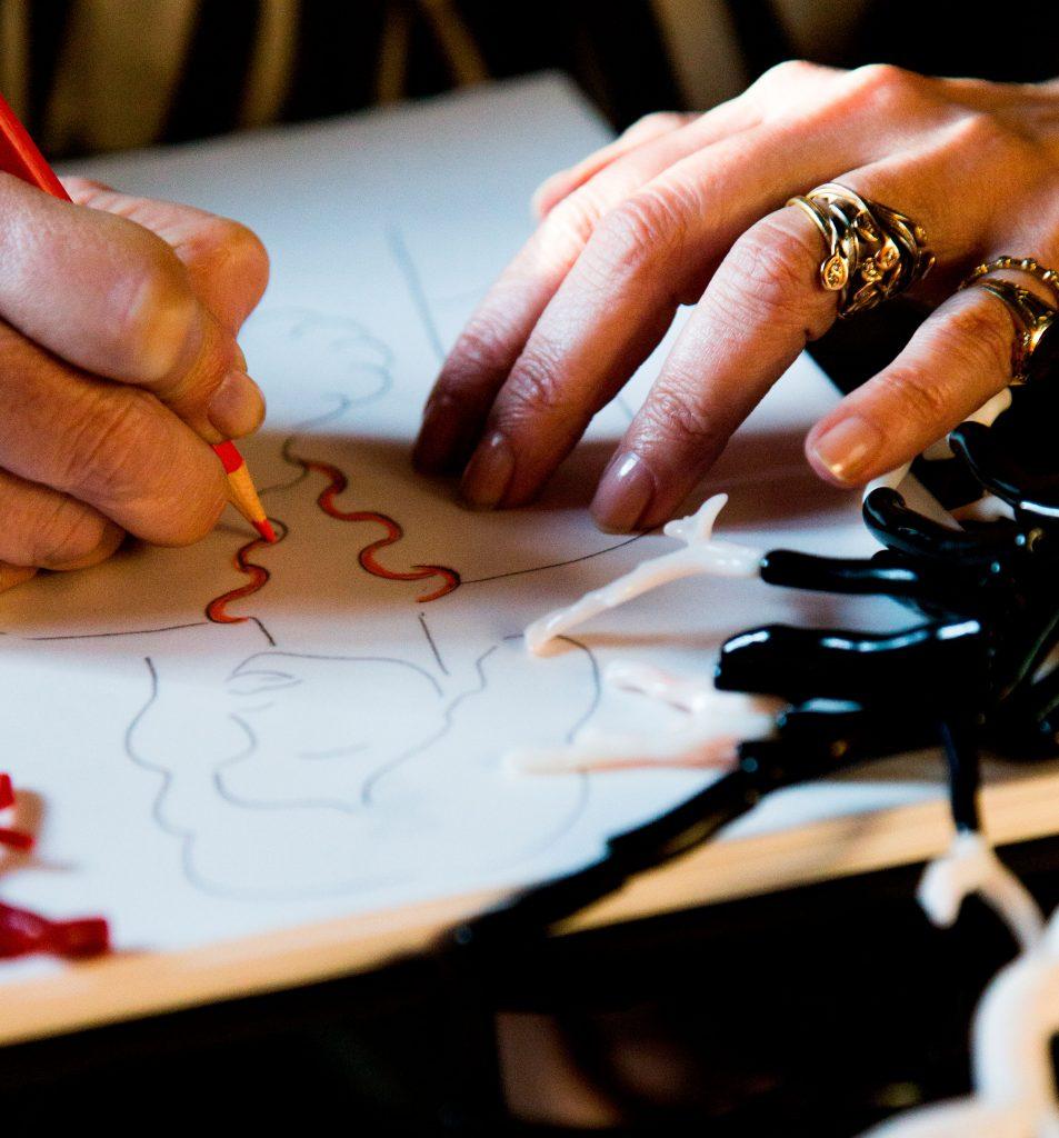 Imagem com a mão da Maria João Bahia a desenhar uma peça no papel.