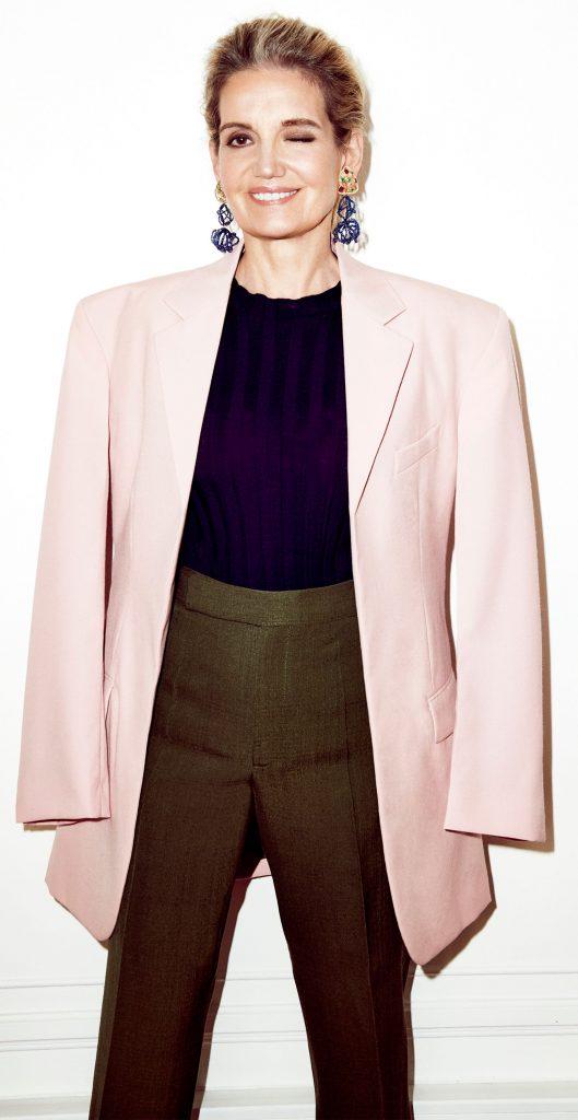 Maria João Bahia a piscar o olho para a fotografia, vestindo calças castanhas, casaco bege e camisola roxa, e usando brincos da sua marca.