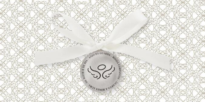 """Medalha em prata para batizado com a frase """"Anjo da guarda, minha companhia, guarda a minha alma de noite e de dia"""". Em cima da medalha, tem um laço branco."""