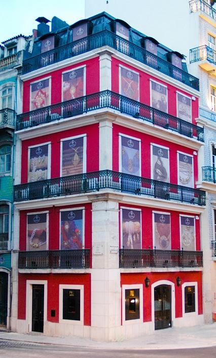 Fotografia do edifício de 4 andares da loja da Maria João Bahia na Avenida da Liberdade. É um edifício pombalino, de cor vermelha.