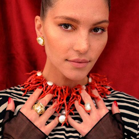 """Fundo vermelho com modelo a posar para a fotografia com brincos, colar e anéis da campanha """"I'MJB"""". Esta campanha traz a essência do design de jóias finas com a assinatura Maria João Bahia."""