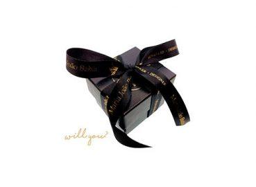 A imagem ilustra um exemplo de embalagem utilizada para embrulhar os anéis de pedido de casamento. É uma embalagem preta, com letras douradas e laço preto e dourado.