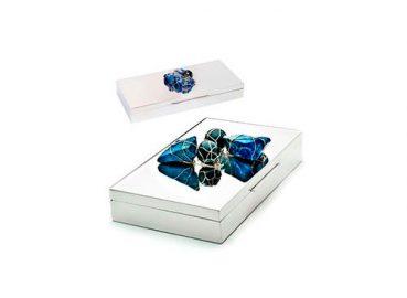 A imagem ilustra as caixas. É uma embalagem preta, com letras douradas e laço preto e dourado.